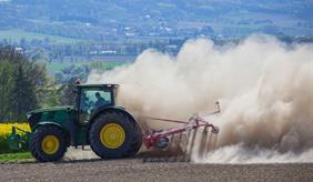 Traktor wirbelt trockenen Boden vom Feld auf
